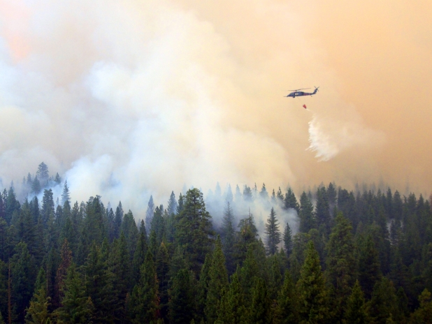 A helicopter flies over a wildfire and drops a large bucket of water to help suppress the fire near Yosemite, Calififornia.