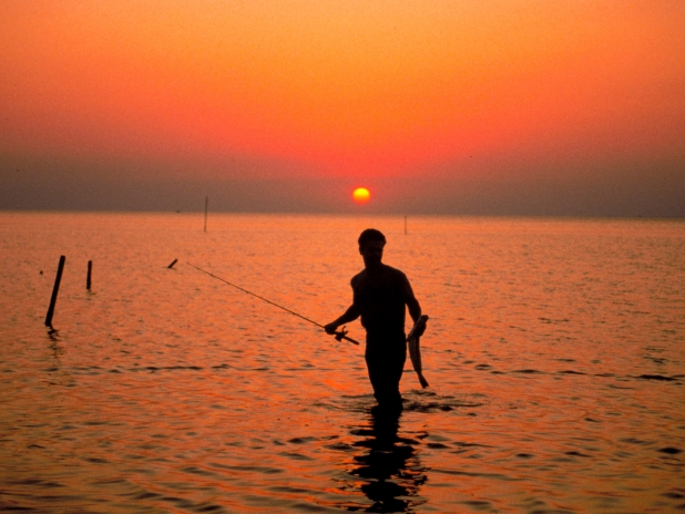 A Man Fishing In The Ocean At Sunset