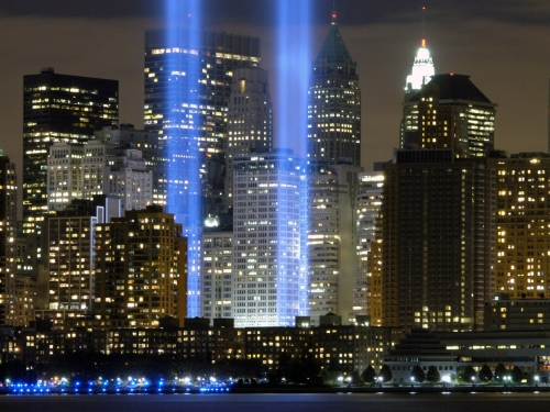 Two columns of light reach into the sky at the site of the World Trade Center in New York City.