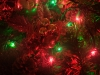 A close-up of a Christmas wreath with red and green lights.